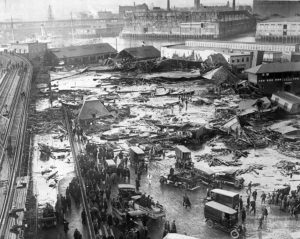 An aerial shot of a neighborhood with most buildings reduced to rubble. The harbor is visible in the distance. A crowd of people and ambulances loiter at the edge of a shallow lake of liquid, with more  walking on it and searching the wreckage.