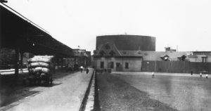 A black-and-white photo of a neighborhood. A bare playground is on the right and an elevated train track is on the left. In the distance, a huge cylindrical tank looms over a row of buildings.